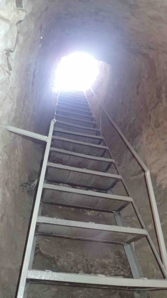 Bright light shining down a metal ladder from a tunnel
