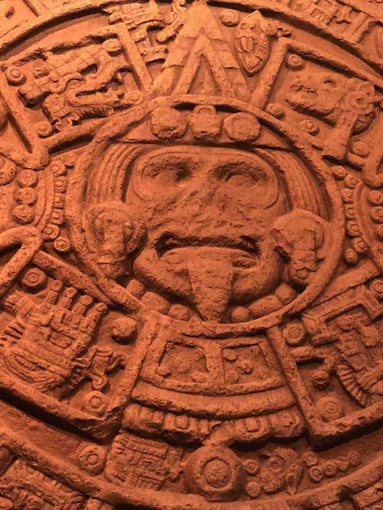 Aztec stone with figure having tongue stuck out