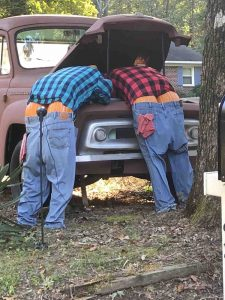 Mannequins with pumpkins for butt cheeks looking under the hood of a car